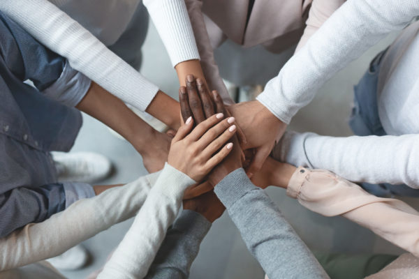 Close up of international business team showing unity with putting their hands together on top of each other. Concept of teamwork, top view